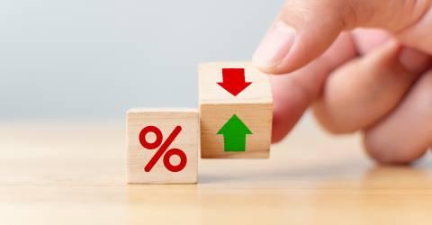 Rente financiële en hypotheekrente concept. Hand flip houten kubus verandering pijl naar beneden naar boven